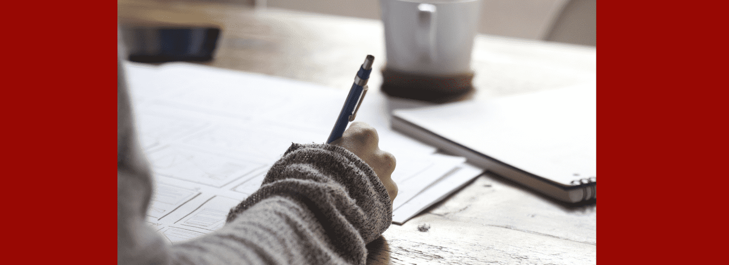 In this picture, there is an arm that extends over some papers, and the person is holding a pencil--about to write.