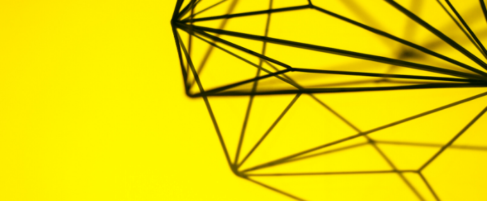 A bright yellow background that has a kind of metal geometric object and its shadow on the right hand side.