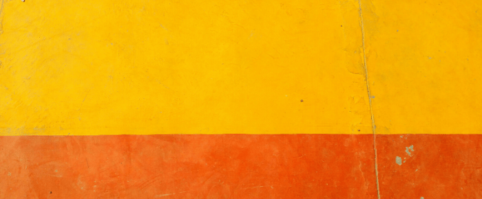 A picture of a wall that is mostly a yellow horizontal stripe, with an orange stripe below it, and a small vertical crack in the wall.
