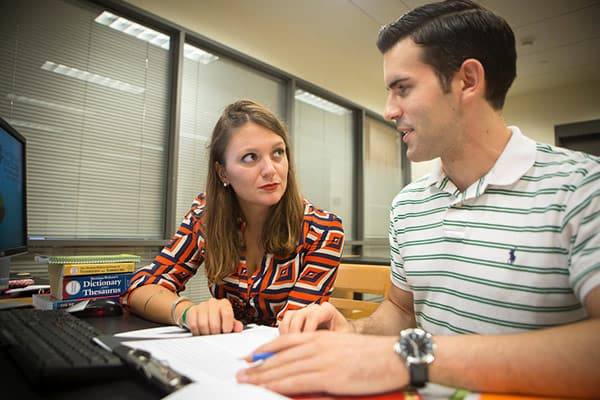 Writing tutor talking with student